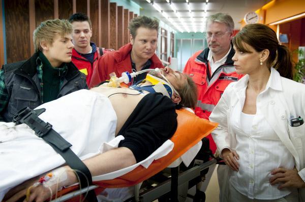 Bild 1 von 7: Michael Jensen (Niki von Tempelhoff, liegend), der Chef einer Baufirma, wird nach einem Sturz von Notarzt Haase (Fabian Harloff, M.) ins EKH eingeliefert. Sein Sohn (Meo Wulf, l.) ist bei ihm, als Jasmin (Gerit Kling, r.) ihn in Empfang nimmt. Im Hintergrund: Komparsen.