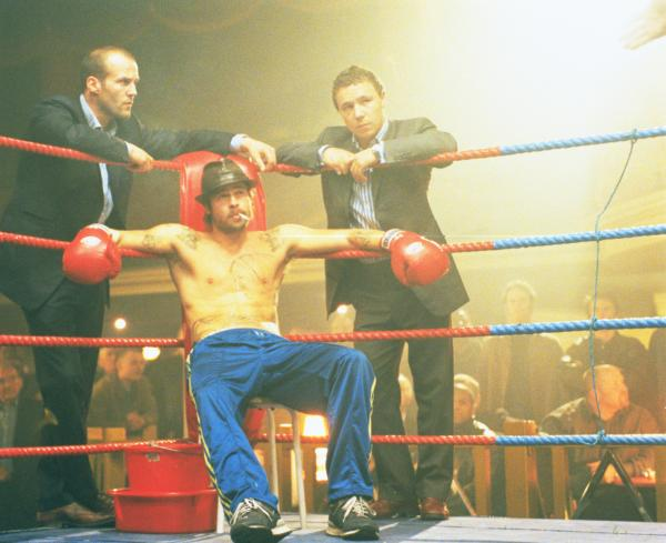 Bild 1 von 3: Mickey (Brad Pitt, M.) ist der Ersatzmann, den Turkish (Jason Statham, l.)  und Tommy (Stephen Graham, r.) für den Boxkampf von Brick Top organisieren konnten.