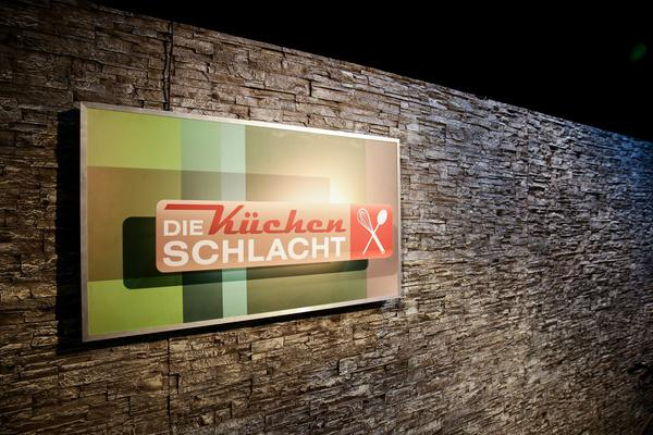 Bild 1 von 2: Das Sendungslogo hängt als Bild in einem Rahmen an einer Wand des Studios.