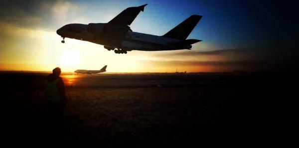 Bild 1 von 3: Dallas Campbell steht neben einer Startbahn und beobachtet, wie ein Airbus A380 abhebt.