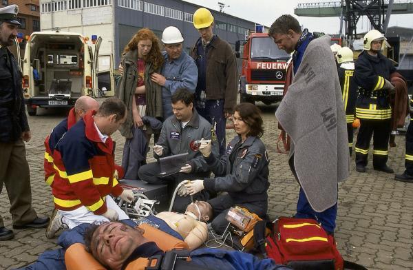Bild 1 von 2: Thomas (Ulrich Bähnk, 3.v.r.) und Ilona (Julia Heinemann, 2.v.r.) kämpfen um das Leben der Verletzten, die bei einer schweren Verpuffung auf der Reparaturwerft verunglückt sind.