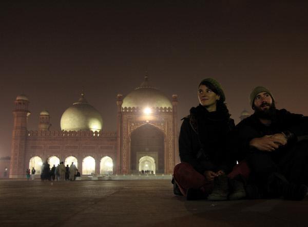 Bild 1 von 5: Gwendolin Weisser (links) und Patrick Allgaier sitzen abends am Rand des Platzes vor der erleuchteten Badshahi Moschee in Lahore, Pakistan.
