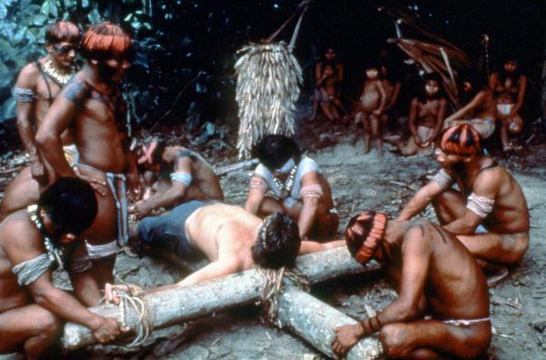 Bild 1 von 7: Eine Gruppe von Eingeborenen bindet einen Priester an ein Holzkreuz und lässt es ins Wasser.