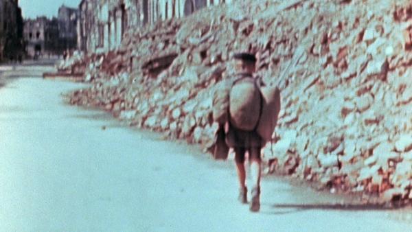Bild 1 von 2: Ein Kind vor den Trümmern einer zerstörten Stadt.