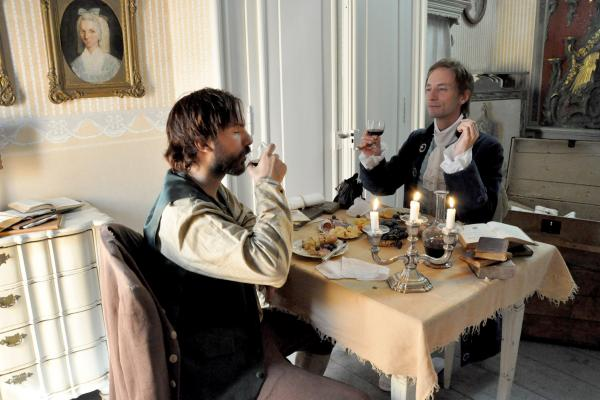 Bild 1 von 3: Winckelmann (Jonas Müller-Liljeström, re.) beim Essen mit seinem späteren Mörder, dem arbeitslosen Koch Arcangeli (David Pfannenschmidt, li.)
