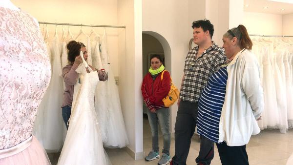 Bild 1 von 7: Ramona, Liesl und John im Brautmodenladen. Sie sehen sich mit Verkäuferin Kleider an...