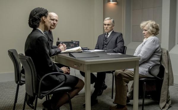 2 Frauen und 2 Männer sitzen in einem sonst leeren Raum an einem Tisch
