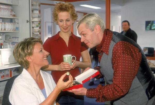 Bild 1 von 8: Tim (Oliver Reinhard, re.) bedankt sich bei Nikola (Mariele Millowitsch, li.) dafür, dass sie ihm gezeigt hat, wie man seine Mitarbeiter zu führen hat. Im Hintergrund beobachtet Postfrau Mona (Jana Ibing) diese Geste.