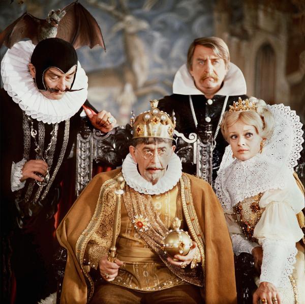 Bild 1 von 2: König Hyazinth (Vlastimil Brodsky, Mitte) bestraft Rumburak für seine Nachlässigkeit. Hofzauberer Vigo (Jiri Sovak, links), die Königin, die aber eigentlich nicht die richtige, sondern die Hexe ist (Jana Andresikova), und ein Mitglied seines Hofstaats schauen zu.