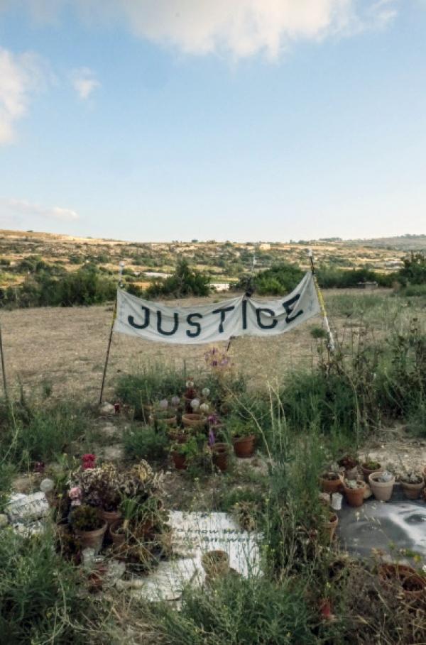Bild 1 von 4: Ein Banner mit der Aufschrift ?Gerechtigkeit? steht auf dem Feld in Bidnija, auf dem das explodierte Auto Galizias landete.