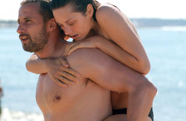 Bild 1 von 2: Ali (Matthias Schoenaerts, l) trägt Ste?phanie (Marion Cotillard) ins Wasser.