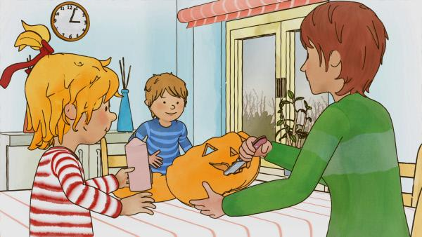 Bild 1 von 4: Mama bastelt mit Conni und Jakob einen Halloween-Kürbis.