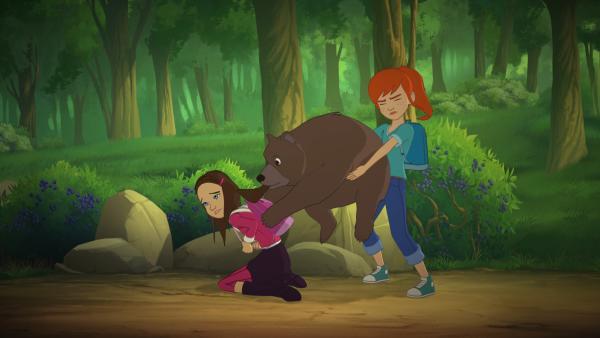 Bild 1 von 3: Samantha (l.) und Zoé (r.) bekommen es mit einem Bärenjungen zu tun, das es auf die Blaubeeren in Samanthas Rucksack abgesehen hat.