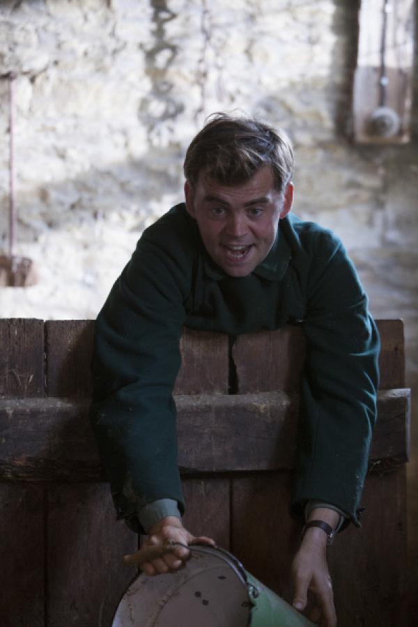 Bild 1 von 5: Sid (Alex Price) wirft den Schweinen Futter hin. Dadurch gelingt es ihm und Father Brown, den verfressenen Schweinen zu entkommen.