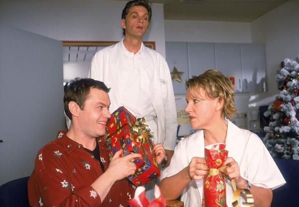 Bild 1 von 10: Tim (Oliver Reinhard, l.) und Nikola (Mariele Millowitsch) packen Weihnachtsgeschenke aus, was von Schmidt (Walter Sittler) neugierig beäugt wird.
