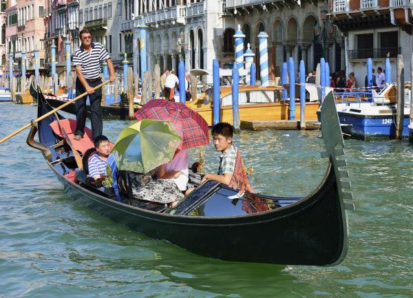 Bild 1 von 2: Chinesische Touristen bei einer Gondelfahrt in Venedig
