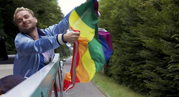 Ein Mann hält eine Regenbogenflagge in der Fahrtwind. Er steht auf  einem Fahrzeug.