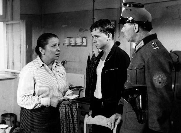 Bild 1 von 4: Ein Polizist liefert Sigi Bernhard (Günther Hoffmann, Mitte) bei seiner Mutter (Edith Schultze-Westrum) ab.