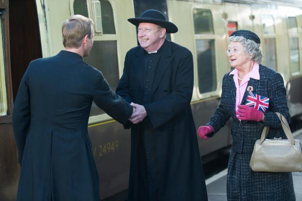 Bild 1 von 2: Father Brown (Mark Williams, M.) und Mrs. McCarthy (Sorcha Cusack, r.)  begrüßen Pater Franc (Rod Hallett, l.) bei seiner Ankunft am Bahnhof.