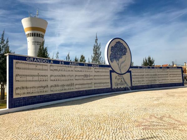 Bild 1 von 9: Monument in Grândola zu Ehren des Komponisten Zeca Afonso (José Manuel Cerqueira Afonso dos Santos), mit dessen Lied die Revolution am 25. April 1974 gestartet wurde. Noten und Text sind auf der Mauer dargestellt.