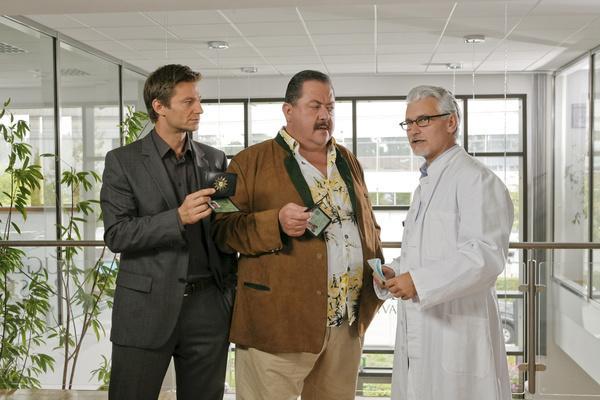 Bild 1 von 2: Dr. Heinz Berger (Alexander Pelz, r.) ist  überrascht, als die Kommissare Korbinian Hofer (Joseph Hannesschläger, M.) und Sven Hansen (Igor Jeftic, l.) ihn zur Tat befragen.