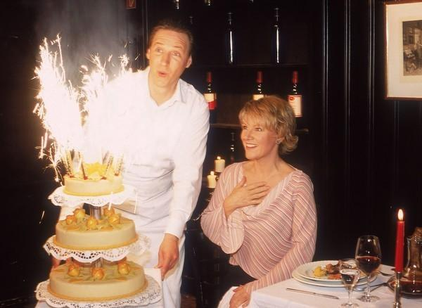 Bild 1 von 7: Kellner Ottmar (Martin Armknecht) bringt eine tolle Torte an Nikolas (Mariele Millowitsch) Tisch, die in dem Restaurant ganz allein ihren Geburtstag feiert. Doch leider ist die Torte nicht für sie...