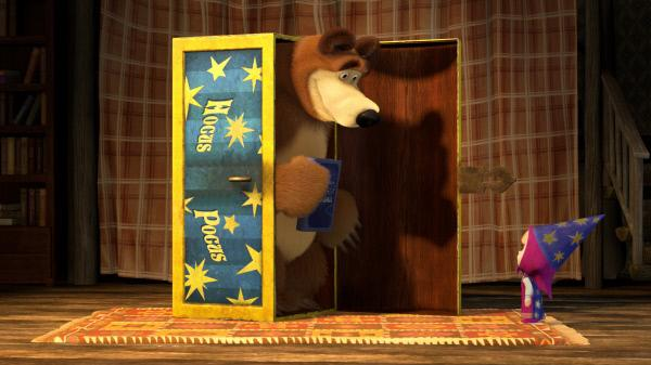 Bild 1 von 2: Es regnet in Strömen. Der Bär will lesen, Mascha will spielen. Da gibt der Bär Mascha einen Zauberkasten.