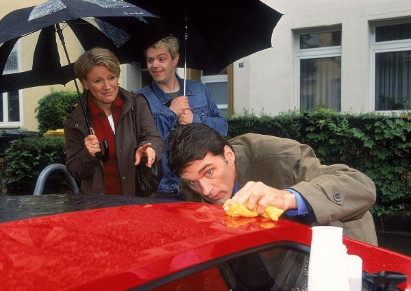 Bild 1 von 6: Selbst bei Dauerregen lässt es sich Dr. Schmidt (Walter Sittler, re.) nicht nehmen, seinen neuen Ferrari zu polieren. Nikola (Mariele Millowitsch) und Tim (Oliver Reinhard) haben dafür nichts als Häme übrig...