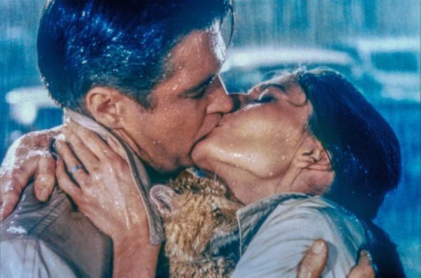 Bild 1 von 5: Holly (Audrey Hepburn) flirtet eifrig mit vermögenden älteren Herren. Der Schriftsteller Paul Varjak (George Peppard) aus ihrer Nachbarschaft, in den sie sich plötzlich verliebt, ist dagegen arm wie eine Kirchenmaus.