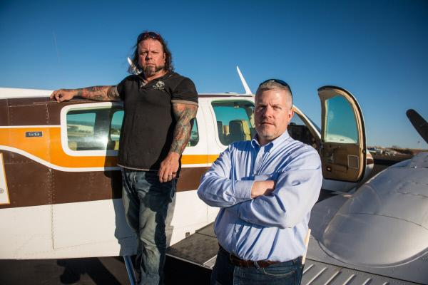Bild 1 von 1: Ken Cage and Danny Thompson outside an airplane.