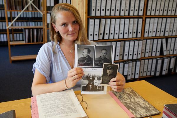 Maria Holzgrewe mit Familienfotos, die ihren Urgroßvater Wilhelm Dreimann zeigen - darunter auch ein Bild mit seiner Tochter. Dreimann wurde von den Häftlingen