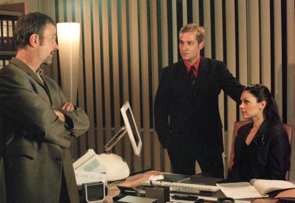 Bild 1 von 3: Kressner (Thomas Anzenhofer, links) droht Alexander Wulf (Niels Bruno Schmidt, Mitte) im Beisein der neuen Sekretärin Yasmin (Burcu Dal).