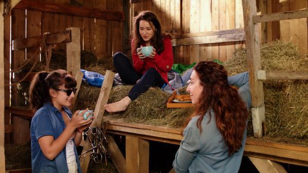 Bild 1 von 5: Nach dem Reservierungsfehler beim Pferdehof findet Mia (Margot Nuccetelli, M.) eine Unterkunft bei Sara (Lucia Luna, l.) und Luciana Poletti (Laura Ruocco, r.).