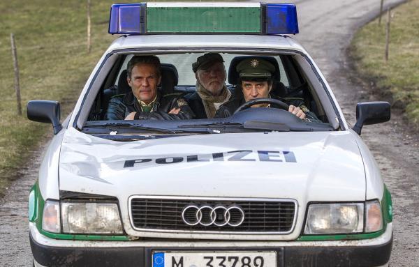 Bild 1 von 4: Johann Eberle (Joost Siedhoff, M.) wird von Hubert (Christian Tramitz, l.) und Staller (Helmfried von Lüttichau, r.) im Polizeiauto aufs Revier gefahren.