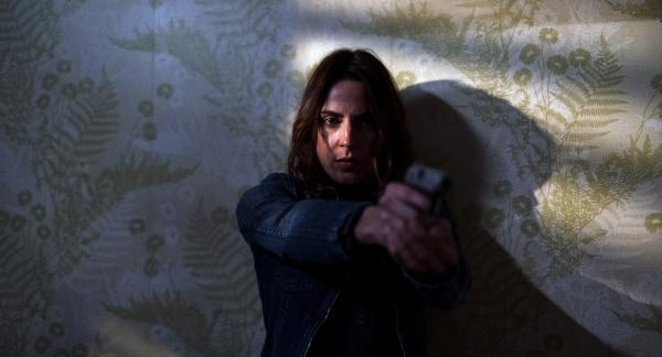 Frau mit Waffe in der Hand zielt