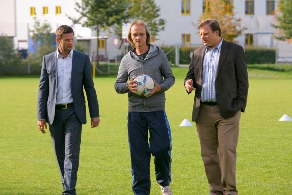 Bild 1 von 3: Mord auf dem Fußballplatz: Erste Ermittlungen führen Hansen (Igor Jeftic, l.) und Hartl (Michael A. Grimm, r.) zu Trainer Rainer Kosinsky (Eisi Gulp, M.).