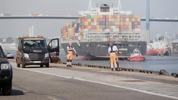 Bild 1 von 5: Arbeiter stehen an einem Anlegekai im Hamburger Hafen.