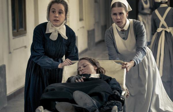 Bild 1 von 12: Ida Lenze (Alicia von Rittberg, M.) wird mit Verdacht auf Blinddarmentzündung in die Charité eingeliefert. Schwester Therese (Klara Deutschmann, l.) und Wärterin Edith (Tanja Schleiff, r.) verlieren keine Zeit.