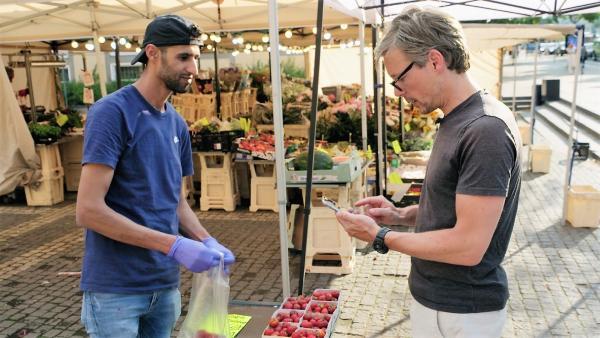 Bild 1 von 3: Stockholm: Am Obststand werden die Erdbeeren mit dem Smartphone bezahlt.