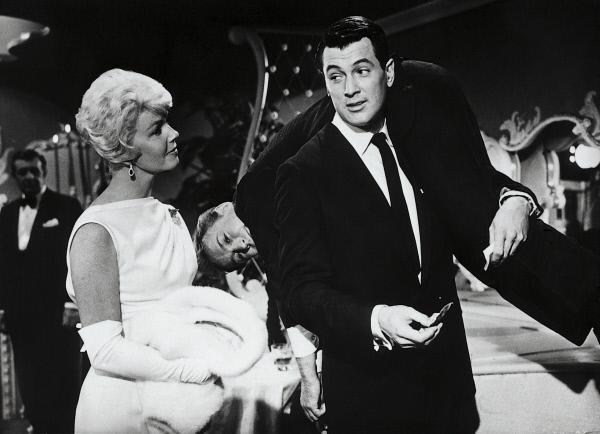 Bild 1 von 4: Als Jan Morrow (Doris Day, l.) mit Toni Walters (Nick Adams, M.) einen Nachtclub besucht, klappt er volltrunken zusammen. In dieser Situation ist der attraktiven Blondine ein vollendeter Kavalier behilflich, der sich als Rex Stetson aus Texas vorstellt. Jan ahnt nicht, dass er in Wirklichkeit Brad Allen (Rock Hudson, r.) heißt und der Mann ist, den sie schon zum Teufel gewünscht hat, weil sie mit ihm eine Telefonnummer teilen muss.