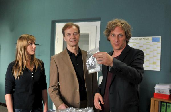 Bild 1 von 5: Die Kollegin von der Spurensicherung (Julischka Eichel, l.) bringt die gefundene Handtasche von Miriam in das Teambüro. Reddemann (Arnfried Lerche, M.) und Ben (Kai Lentrodt, r.) finden darin Miriams Asthma-Spray.