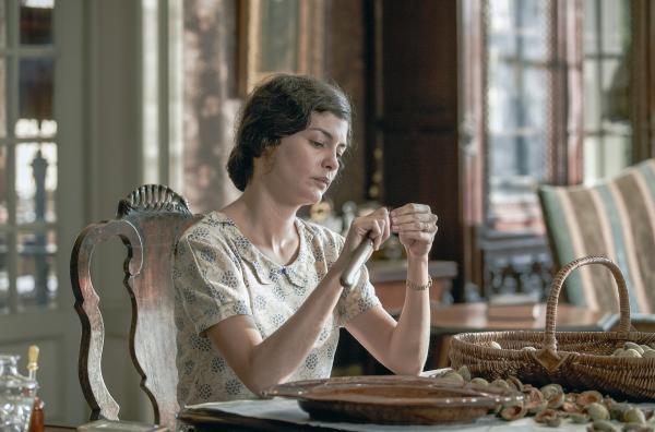 An einem Tisch sitzt eine gelangweilte schöne junge Frau mit braunen Haaren