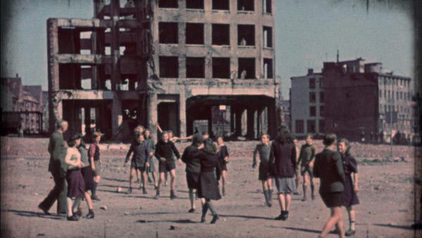 Bild 1 von 2: Kinder vor zerstörtem Haus.