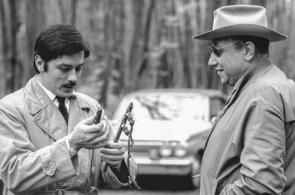 Bild 1 von 4: Alain Delon (li.) und Jean-Pierre Melville (re.) während der Dreharbeiten zu dem Gangsterfilm \