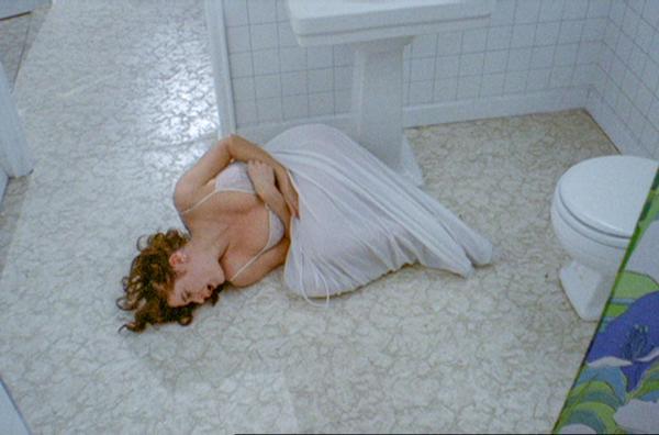 Eine Frau liegt nur mit einem Handtuch umschlungen und trägt einen weissen BH am Boden eines Badezimmers