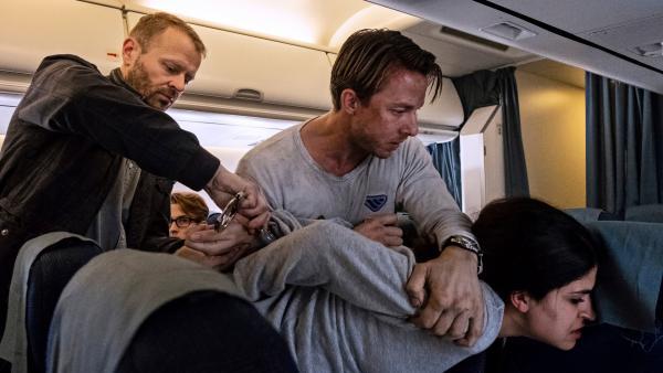 Bild 1 von 5: Philip Nørgaard (Johannes Lassen) überwältigt June al-Baqee (Yasmin Mahmoud) im Flugzeug, da diese nicht will, dass er ihr Handy an die Russen weitergibt.