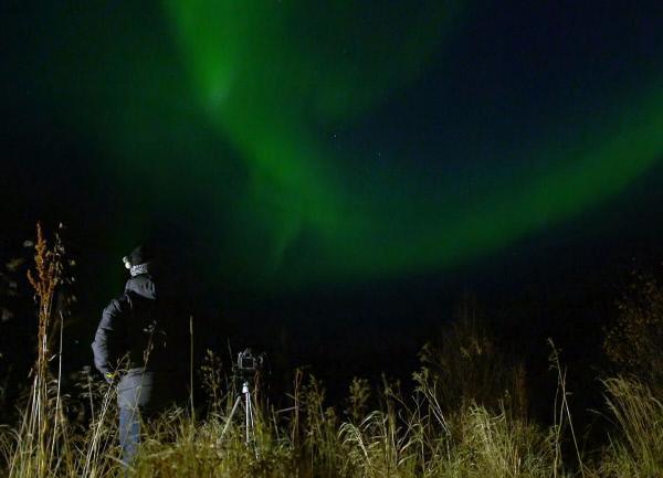 Bild 1 von 3: Meteo-Mann Christoph Siegrist und Polarlichter über Ersfjordbotn in Norwegen