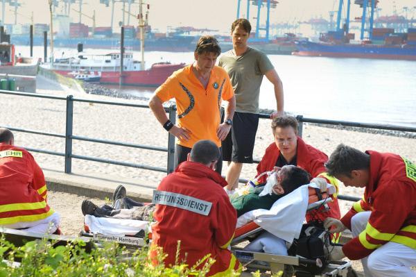 Bild 1 von 13: Mattes (Matthias Schloo, hinten r.) und Henning (Uwe Fellensiek, hinten l.) haben beim Joggen einen schwer verletzten Asiaten (Komparse) gefunden und sofort Notarzt Haase (Fabian Harloff, 2.v.r.) und sein Team (Komparsen) zu Hilfe gerufen.
