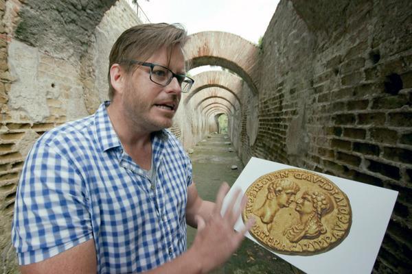 Bild 1 von 4: Archäologieprofessor Kevin Dicus mit einer Münze aus dem ersten Monat von Neros Regierungszeit, die den Kaiser mit seiner Mutter Agrippina zeigt.