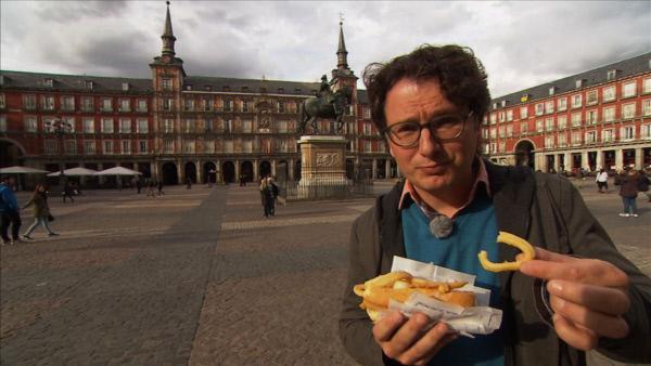 Bild 1 von 6: Moderator Michael Friemel probiert auf der Plaza Mayor eine madrilenische Spezialität: Bocadillo con Calamares, Brötchen mit Tintenfinschringen.